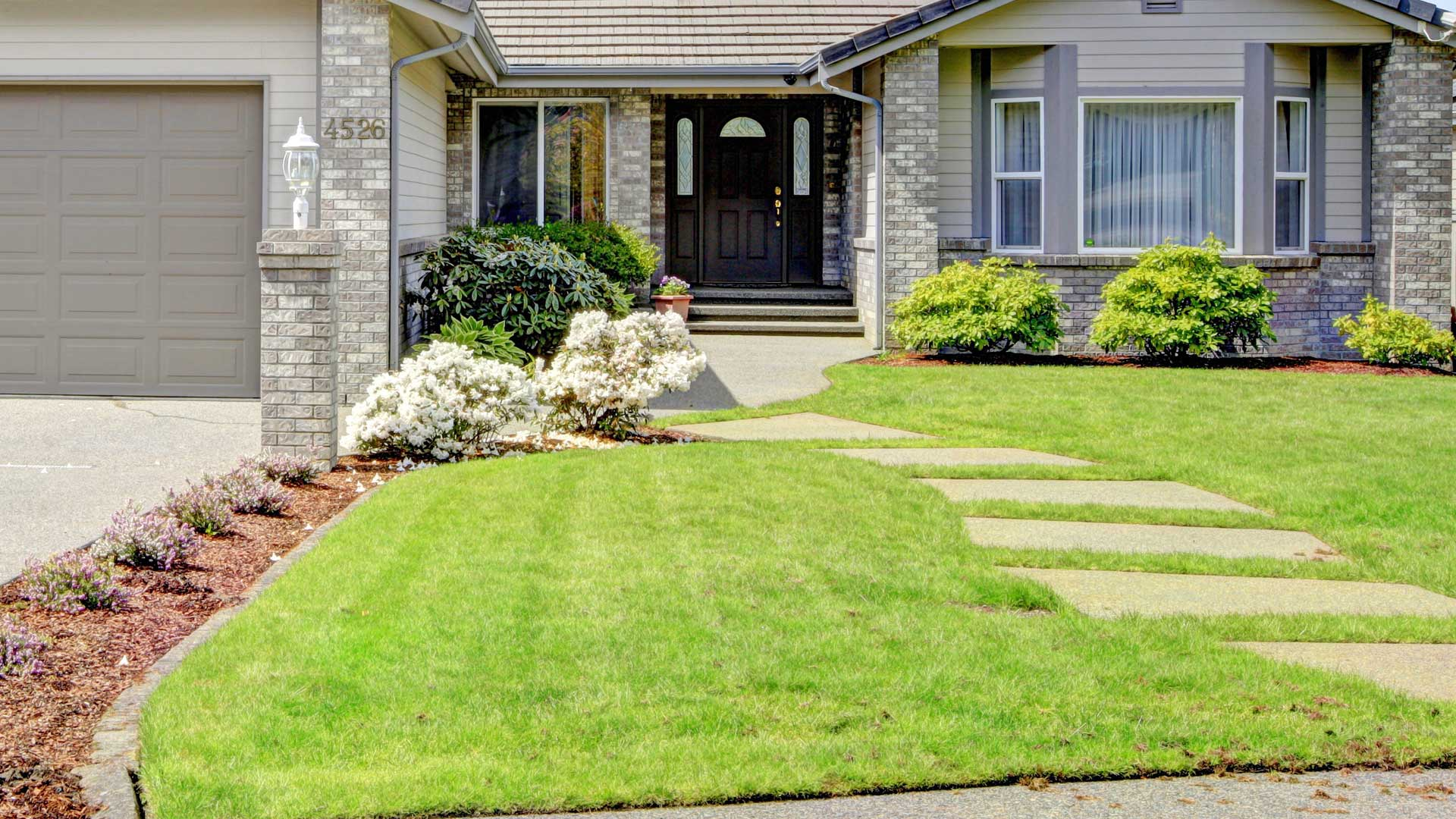 Mowed lawn and maintained landscaping by J&C Lawn Care.